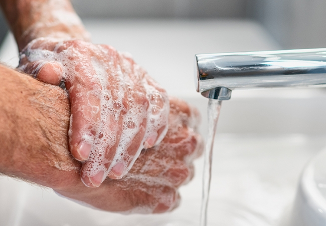 man washing his hands protecting the office